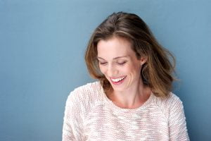 woman in pink sweater laughs, standing against a blue backdrop
